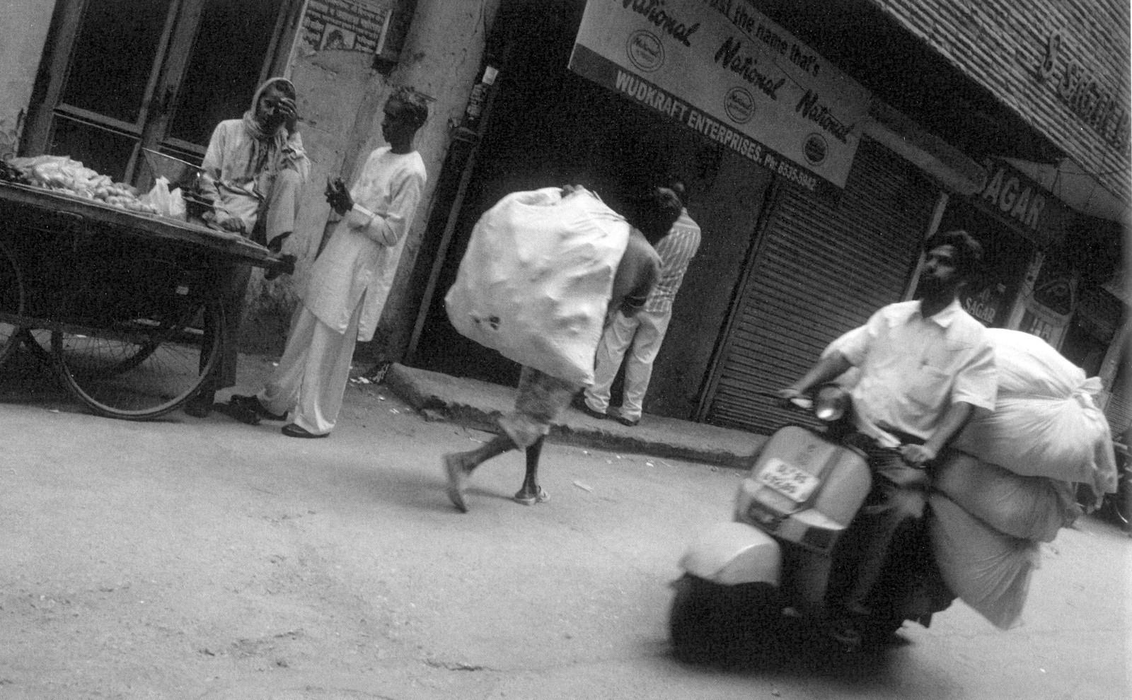 Fotografía en blanco y negro de una calle de nueva delhi en la India. Motocicleta repartiendo sacos