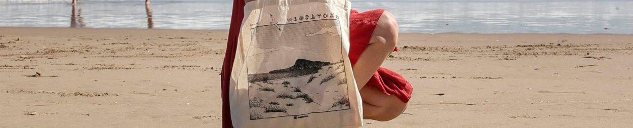 Fotografía con modelo de un diseño de bolsa de tela tote con un dibujo de la playa de oliva en valencia