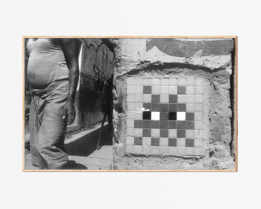 Lámina blanco y negro foto de un indio frente a un mosaico del artista urbano Space Invaders en Varanasi, India