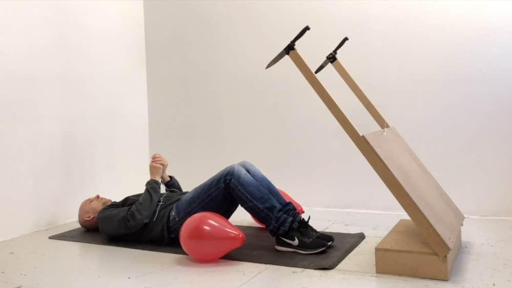 Fotografia del artista jan erichsen explotando dos globos con uno de sus inventos