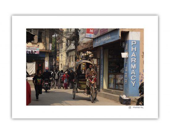 Fotografía en color de una calle de Kathmandu en Nepal. En la imagen aparece un ciclo rickshaw y una farmacia