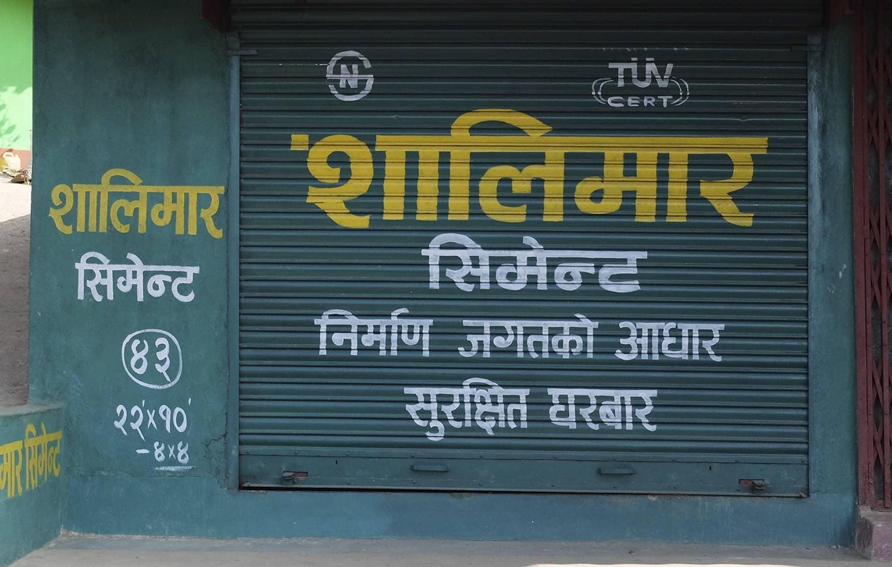 Fotografía en color de un graffiti con un diseño gráfico espectacular. Puerta de un negocio en Ilam, Nepal. Arte